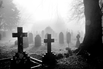 black and white photograph of an English grave yard covered in thick fog