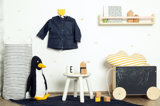 Cute corner in the nursery room in white, black and yellow colors