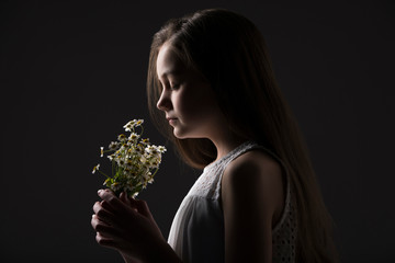 Side view of cute girl with eyes closed smelling flowers while standing against black background