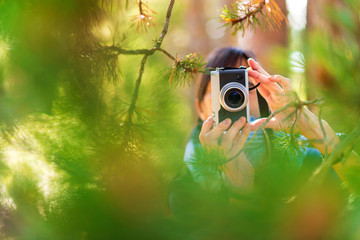 Female hiker photographing with camera while standing by plants in forest