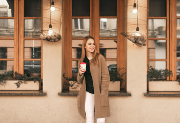 Happy girl in a coat and a cup of coffee in her hands, wearing a coat, stands on the background of the brown wall and the restaurant window, looking sideways and smiling.