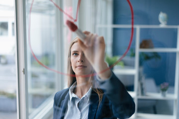 Young businesswoman drawing a pie chart on a glass screen