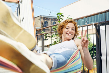 Happy young woman in hammock making victory sign in urban surrounding