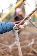Dickes Seil mit Verbindung und Kinderhand. Strong rope at playground.