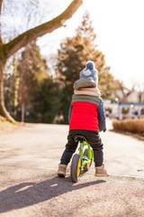 Kind färt mit Laufrad im Park im Herbst. Kid ride balance bike in park in fall.