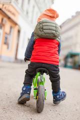 Kid ride balance bike on city street. Kind färt mit Laufrad auf Straße.