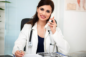 Young female doctor working at office desk and answering phone calls