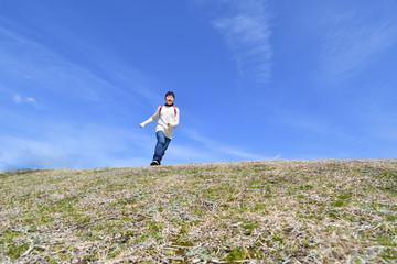 青空で走る小学生の女の子(ランドセル)
