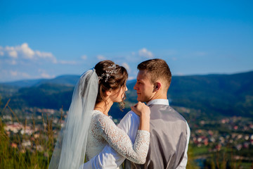 Newlyweds smile and hug each other among the meadow on top of the mountain. Wedding walk in the woods in the mountains, the gentle emotions of the couple, photo for Valentine's Day