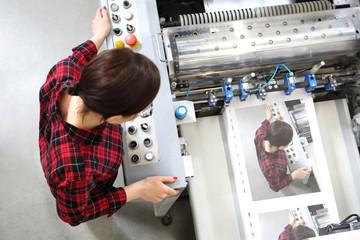 Fototapeta Drukarnia. Kobieta pracuje przy maszynie foliującej. obraz