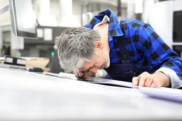 Fototapeta Drukarz przy stole montażowym ogląda przez lupę jakość wydruku. obraz