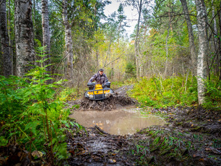 A man rides on ATV through the mud. Riding a quad bike. A man rides an all-terrain vehicle. Riding off-road on an ATV. Outdoor activity. Extreme. Rent a quad bike.