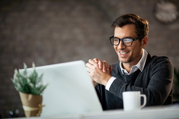 Happy male entrepreneur using laptop while working in the office. Wall mural