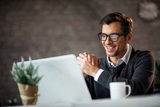 Happy male entrepreneur using laptop while working in the office.