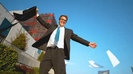 SLOW MOTION Young businessman throws paperwork in the sky after quitting his job