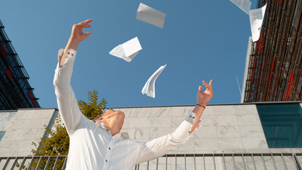 SLOW MOTION: Happy young man throws papers into the air after getting promoted.