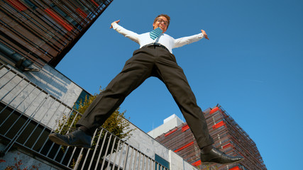 LOW ANGLE: Cheerful businessman jumps and outstretches his arms after work.