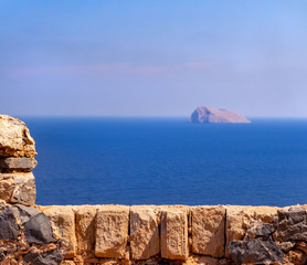 Detail of ancient fort wall - blue sea and small rocky island in the background
