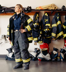 Woman firefighter at fire station. Confident, proud public service career professional.