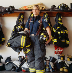 Smiling woman firefighter at fire station. Confident, successful public service career professional.