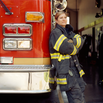 Thoughtful female firefighter leaning on fire engine