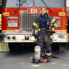 Portrait of female firefighter with equipment standing near fire engine