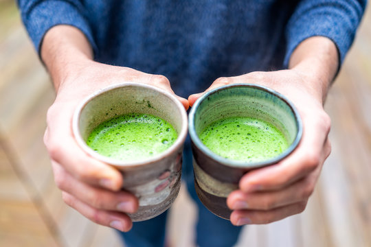 Closeup of man person hands holding two tea cups outside on backyard deck wooden bokeh background in garden drinking matcha green drink