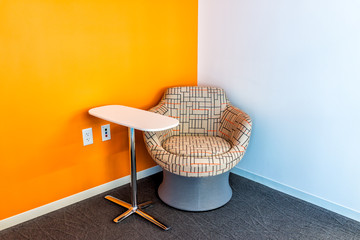 New modern office room or university hall in building with vibrant blue orange chair in corner and small table by wall empty and nobody
