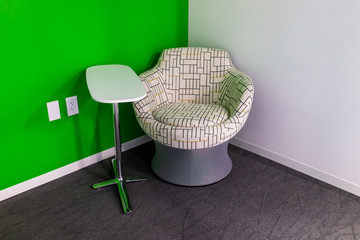 New modern office room or university hall in building with vibrant green chair in corner and small table by wall empty and nobody