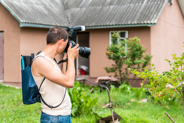 Young man photographer in garden taking picture photo of plants and house cottage real estate in green summer in Ukraine dacha