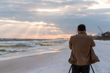 Dramatic sunset with sun rays beams in Santa Rosa Beach, Florida with back of young man photographer standing taking picture looking at coastline coast