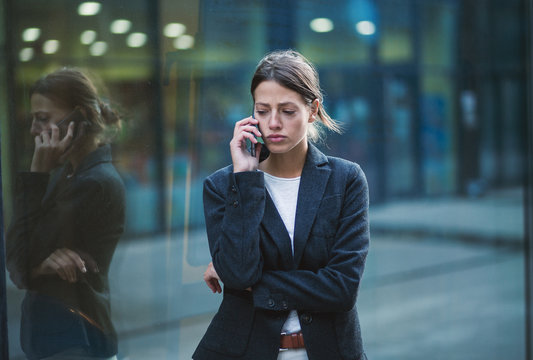 Unhappy business woman talking on the phone