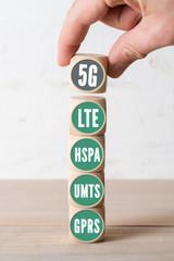 Hand stapelt Würfel mit Mobilfunktechnologien, 5G als oberstes