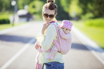 Cheerful Caucasian woman carrying her baby daughter on back