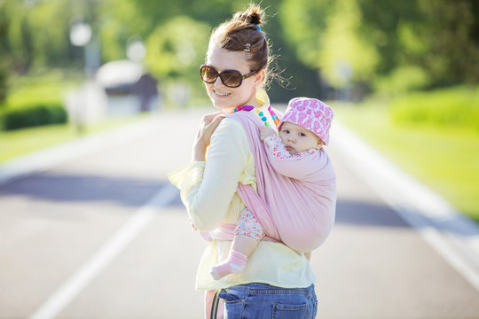 Cheerful Caucasian woman carrying her baby daughter on back outdoors