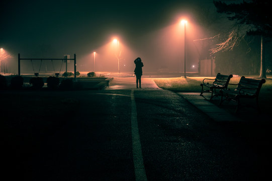 Figure stands at end of foggy path lit by streetlights.
