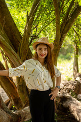 Women white skin lovely brown hair wearing a basketry hat brown red lip wear white shirt wearing black pants women standing poses photography portrait under the tree In the garden.
