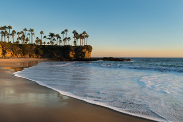 Shore with palm trees, rocks, blue sky and ocean in sunset time. Soft sunlight falling on beach....