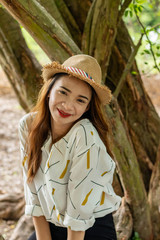 Women white skin lovely brown hair wearing a basketry hat brown red lip wear white shirt wearing black pants women sit poses photography portrait under the tree In the garden.