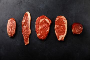 Variety of Raw Black Angus Prime meat steaks Top Blade,  Top sirloin cap, Rib Eye, Striploin, Tenderloin fillet Mignon on dark background