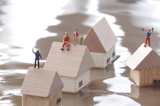 水害で浸水した家の上で救助を待つ人々
