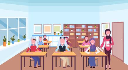 muslim teacher reading book during lesson arabic pupils in hijab sitting desks education concept modern school classroom interior horizontal full length flat