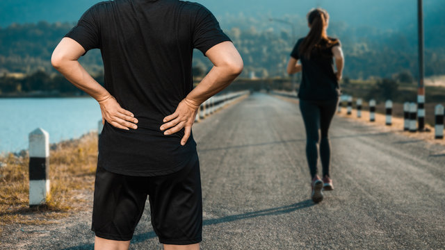 Young man on running road in the outdoors having a back pain.