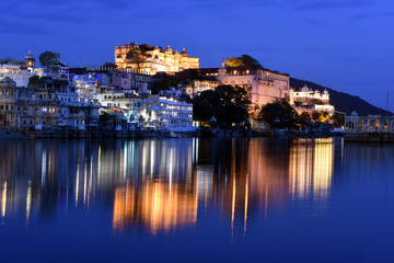 Wall Mural - panoramic sunset view of city palace at Lake Pichola from Ambrai Ghat at Udaipur, Rajasthan, India