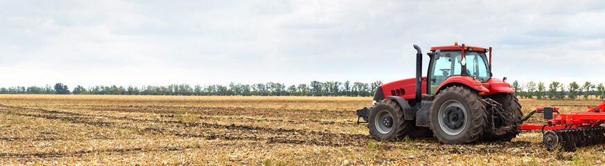 Fototapete - Tractor with plow working in the field