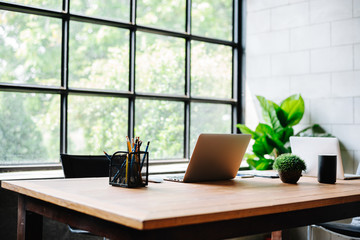 Image of an homeoffice interior with wood desk work. Computers and office supplies with no employees .