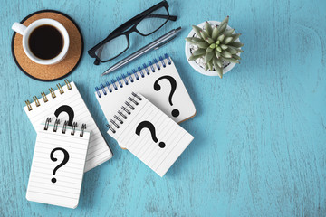 Question marks on notepads on blue wooden background