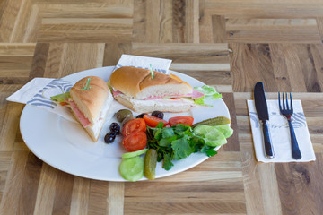 Sandwich with cheese,ham,tomato and lettuce on a wooden table