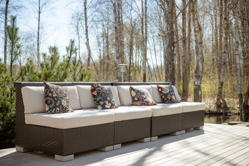 Large terrace with rattan garden furniture set.Wooden garden lounge chair with cushion. comfortable rattan sofa. relaxing area outside .patio with furniture on wooden floor.relaxation on the terrace
