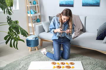 Female food photographer with mobile phone taking picture of tasty cookies and orange slices at home